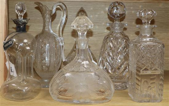 A dimple glass silver-mounted decanter with silver whisky label, a cut glass claret jug and four decanters and stoppers