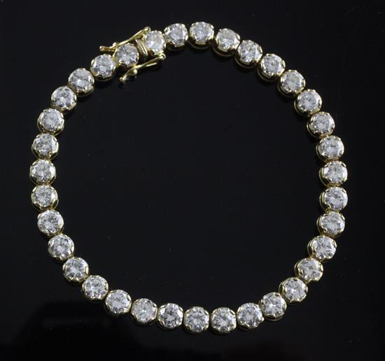 An 18ct gold and diamond line bracelet, 18cm.