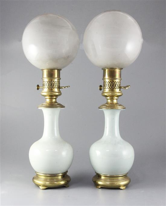 A pair of mid 19th century French ormolu mounted celadon porcelain oil lamps, with opaque circular glass shades, height 23in.