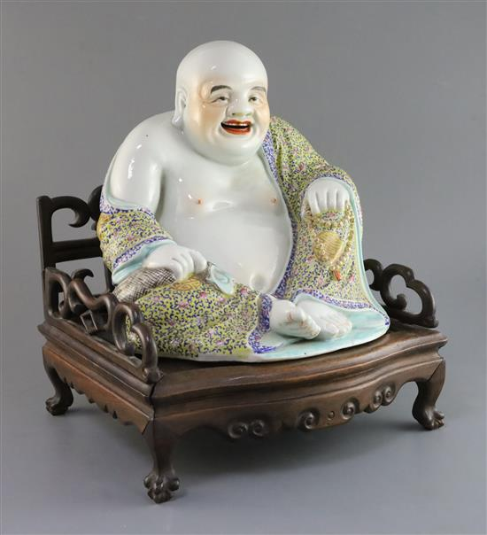 A Chinese famille rose seated figure of Budai, Republic period, H. 27cm, excluding hongmu throne stand