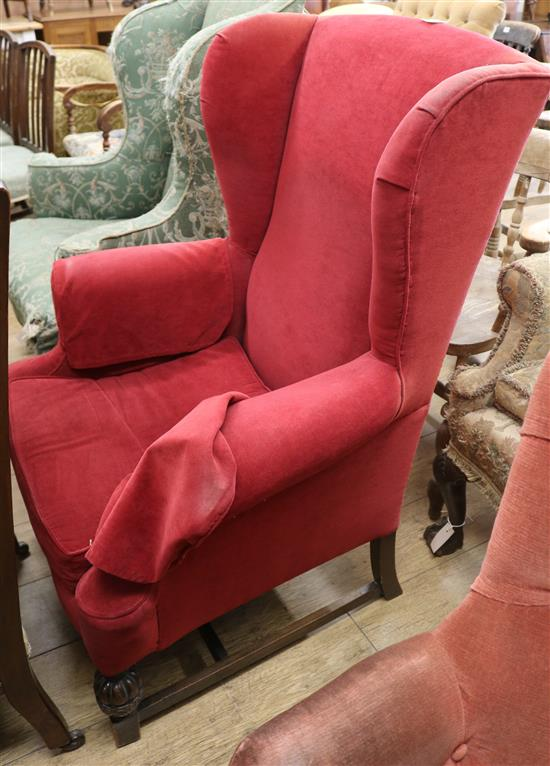 A Georgian style upholstered wing armchair