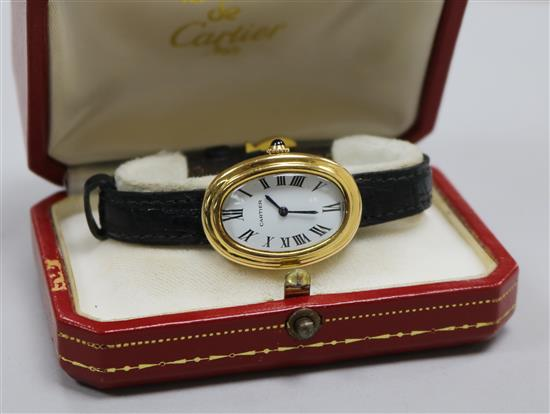 A ladys 18ct gold Cartier oval cased wrist watch, with Cartier box.