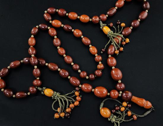 A Persian gilt metal and graduated amber bead tassel drop necklace, 180cm incl. tassel.
