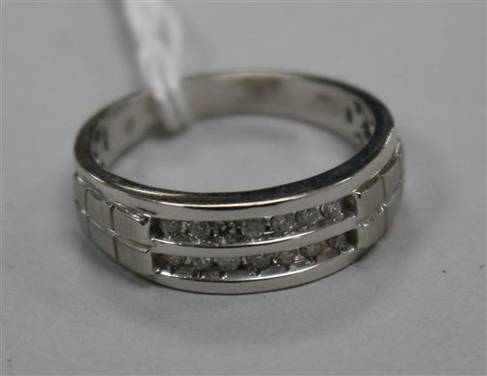 A modern 10ct white gold and two row channel set diamond half hoop ring, size W.