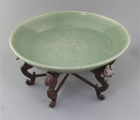 A Chinese Ming dynasty Longquan celadon dish, 15th century, d. 45cm, hongmu stand,